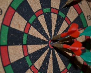 dartboard with several arrows in the bullseye
